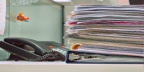 Akten stapeln sich vor Telefon auf Schreibtisch