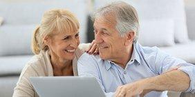 Ältere Frau und älterer Mann sitzen am Laptop und lächeln