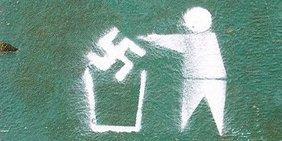 Graffiti: Figur wirft (Nazi-)Hakenkreuz in Papierkorb