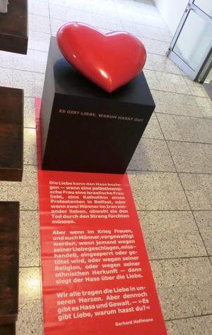 Die Installation in Form eines großen roten Herzens auf einem Pult, darunter eine schriftliche Erlauterung zur Installation auf roter Folie gedruckt.