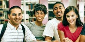 4 Jugendliche aus 4 verschiedenen Kulturkreisen lächeln in die Kamera