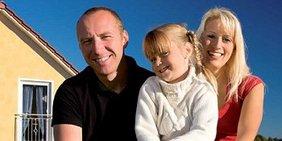 Familie mit kleiner Tochter vor Eigenheim