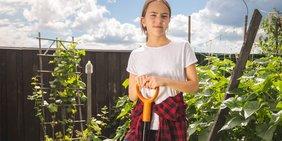 Mädchen/Jugendliche bei sonnigem Wetter im Garten (blickt in Kamera, hält Spaten in der Hand)