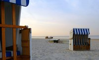 Strandkorb im Hintergrund ein Holzschiff im Meer.