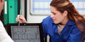 Handwerkerin zeigt auf Laptop