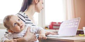 Mutter arbeitet zu Hause am Laptop und hält ein Kleinkind im Arm