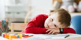 Trauriger Junge mit Büchern am Schreibtisch
