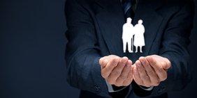 Silhouette Senioren-Paar schwebt über den Händen eines Geschäftsmanns