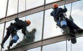 Gebäudereiniger hängen in dürren Seilen an einer Hochhausfassade und wischen Scheiben