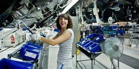 Frau bei der Automontage am Fließband