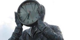 Statue Mann hält sich große Uhr vor das Gesicht