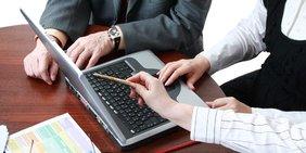 3 Arbeitskollegen arbeiten gemeinsam an einem Laptop