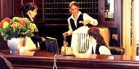 3 Hotelangestellte an Rezeption im Gespräch, eine hält frisch gereinigte Kleidung hoch