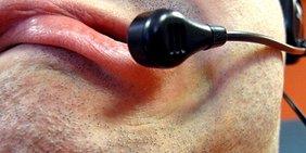 Skeptisch verzogener Mund eines Mannes hinter einem Headset-Mikrofon
