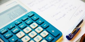 Taschenrechner, Stift und Zettel mit Berechnung